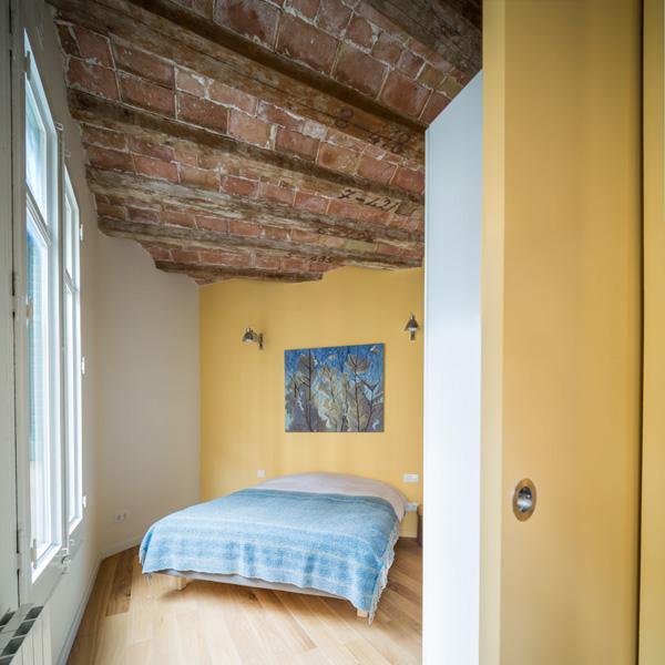 קיר צהוב וקורות תקרה חשופות בחדר השינה