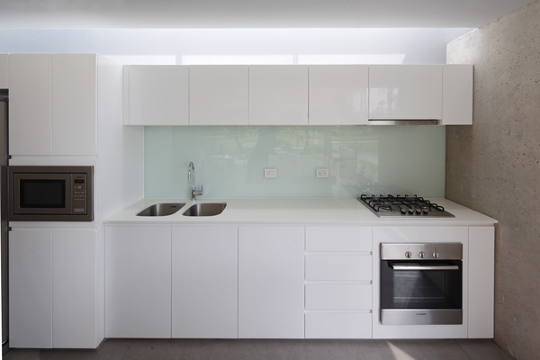 המטבח עוצב בגוון לבן עם חיפוי קיר מזכוכית