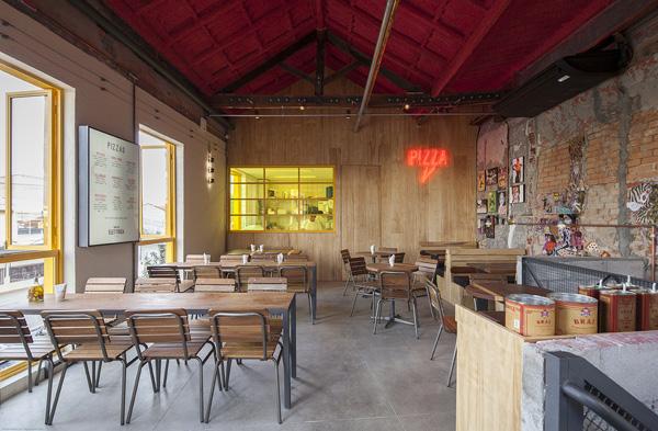 בקומה השניה חלון צהוב שחושף את המטבח, וקיר שמחופה עץ אורן בהיר