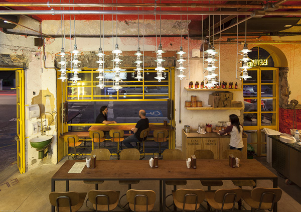 קומת הכניסה לפיצריה כוללת שולחנות ארוכים לארוחה שיתופית