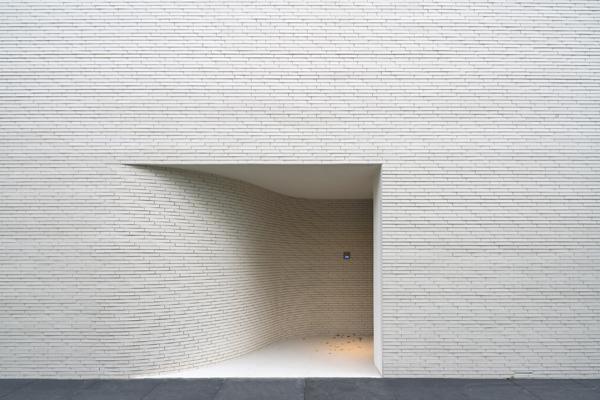 הכניסה לבית מוסווית בקיר הלבנים שפונה אל הרחוב