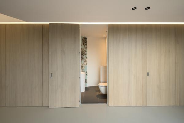 קיר העץ ההמשכי שבקומת הכניסה מסתיר מאחוריו מגוון פונקציות, כמו שירותי אורחים