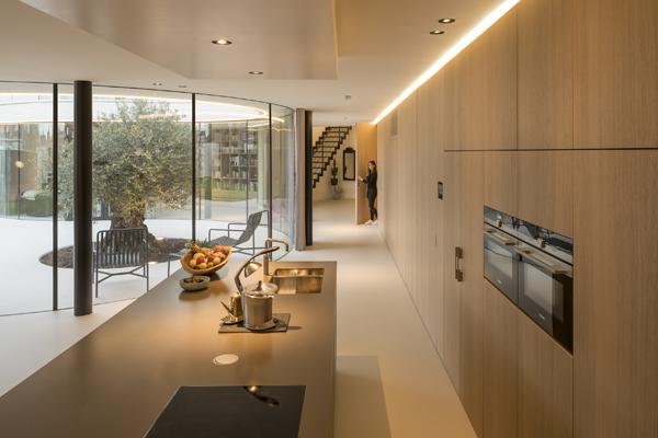 קיר עץ המשכי מסתיר מאחוריו מטבח, שירותים, מזווה ודלת גישה למרתף