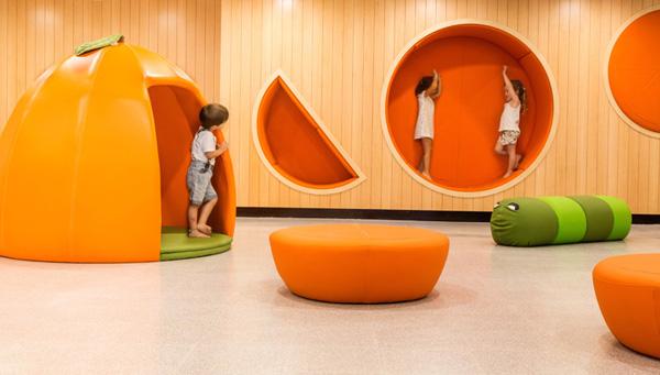 קירות הלובי משלבים גומחות ישיבה מרופדות המעוצבות כתפוזים ומזמינות את הילדים לשבת, לקרוא ולנוח בתוכן. עיצוב: שרית שני חי. צילום: דודי מוסקוביץ