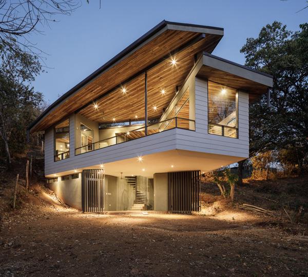 בית העלה המרחף מואר בשעות בין ערביים. תכנון: LSD Architects. צילום: Fernando Alda