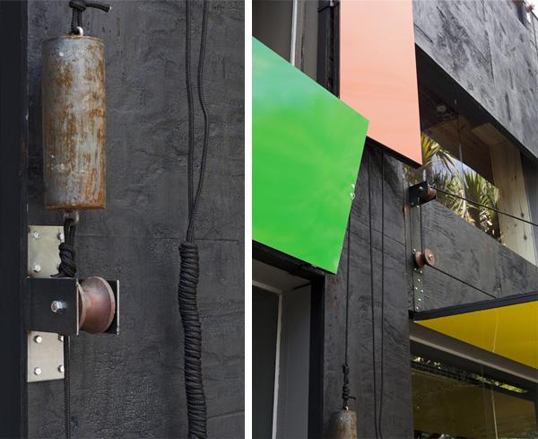 פרט מחזית הבניין שחופתה בלוחות עץ שרופים וגלגלות עם משקולות תעשייתיות לסגירת החלונות, צילום: מריה אקייבה