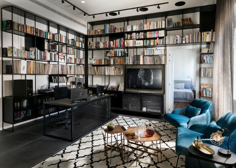 כוננית הברזל מכילה אוסף תקליטים גדול ומחשבים, הסלון ואיזור העבודה בלתי נפרדים צילום: אלעד גונן.