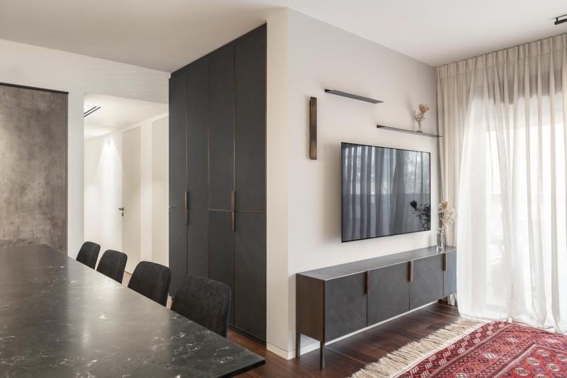 מבט לכיוון פינת קיר סלון עם ארון בר המשקאות בנישה שסופחה למטבח, קרדיט צילום: יואב פלד צילום אדריכלות